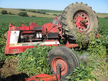 A color image of a tractor that has turned over.